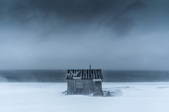 A wooden cabin over the Artic ocean during the severe snow wind but perfect for isolation.