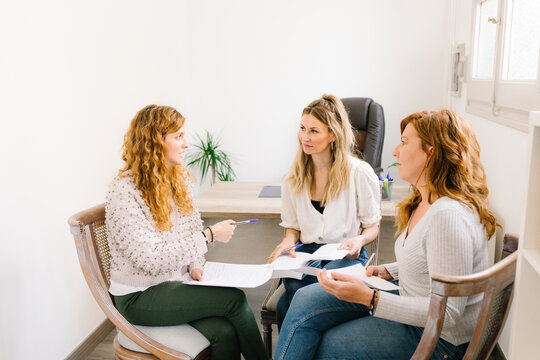 Three women dressed casually in jeans at a business meeting.
