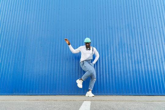 Black Man Dancing on Blue Wall
