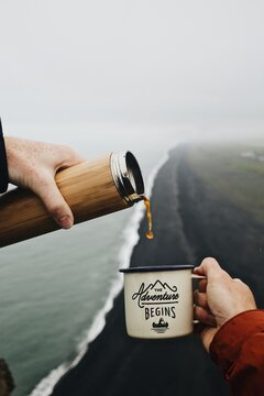 Two hands pouring coffee into the adventure begins mug above a black sand beach in Iceland