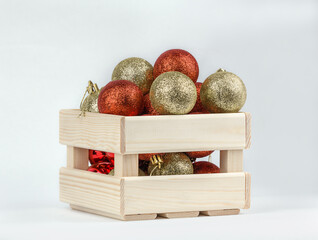 Christmas red and yellow bauble decor in wooden box on white wooden table.