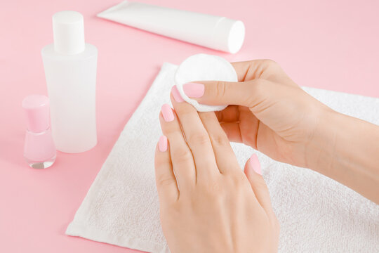 Young adult woman hand removing pink nail polish with white cotton pad on towel on light pink table background. Closeup.