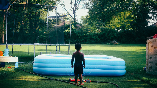 A young boy standing in a grassy backyard in the summer during quarantine using his imagination while playing in the sprinkler by the pool and trampoline