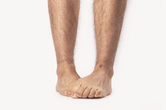 Closeup of the feet of a shy male standing against a white background