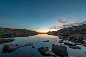 Gorgeous view of a calm lake surrounded by rocks, with the sky reflected on the water during sunset
