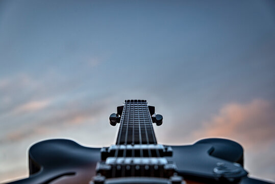 semi hollow guitar against a colorful dusk sky