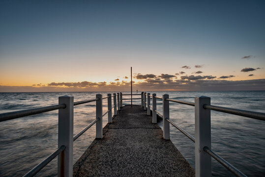 Looking out over a pier against the ocean, a dusk horizon sky