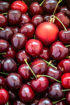 A red christmas bauble amongst ripe red cherries, vertical