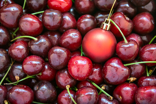 A red christmas bauble amongst ripe red cherries, horizontal