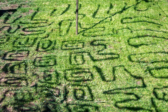 Shadows from military camouflage netting onto grass
