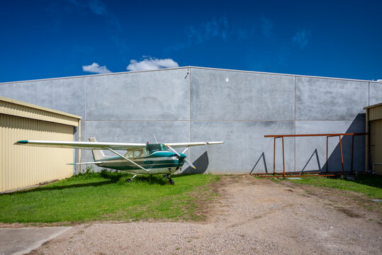 An older Cessna appearing lonley against a concrete wall and yellow hanger against a blue sky and a few clouds