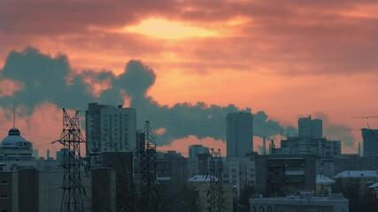 Fotobehang - Smokestacks emitting smoke in sunset sky over dark winter city skyline silhouette. Timelapse, 4K UHD.