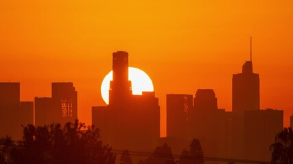 Fotobehang - Downtown Los Angeles. Sunrise sun over city buildings silhouettes, zoom out. Timelapse, 4K UHD