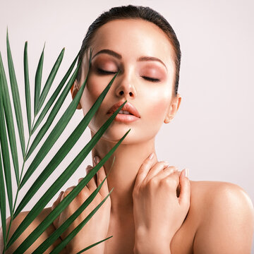 Young beautiful woman with green leaves near naked body. Body care beauty treatments concept.  Girl's  face with green flowers.