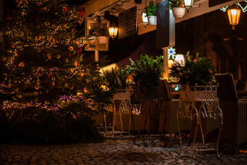 A cozy street cafe with Christmas decorations on the street of the old town in Prague. Christmas illumination. Bokeh garlands in the background. Christmas, winter, new year concept. Fotomurales