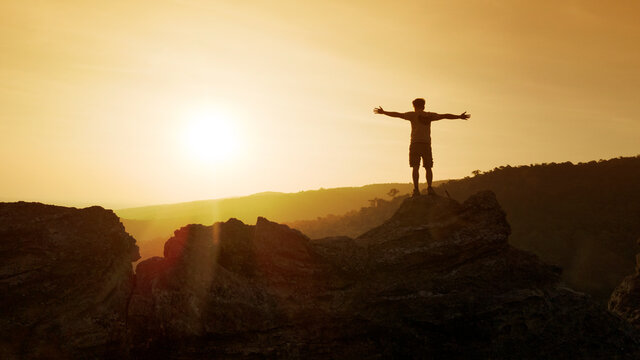 man open arms on top of mountain with sunset or sunrise background