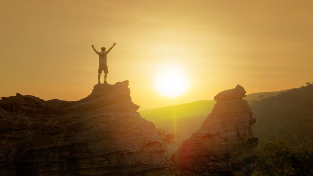 man raise hands on top of mountain with sunset or sunrise background