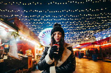 A pretty girl in winter clothes stands at the Christmas market in the evening with beautiful decorations, drinks mulled wine and looks at the camera. Lady walks along the street decorated with light Fotomurales