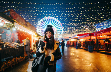 Attractive girl in warm clothes walks around the evening Christmas market with a cup of hot drink in hands, looks at the camera with a smile. Lady with a cup of coffee on a Christmas street background Fotomurales