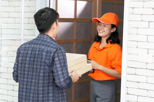 Food delivery service woman in orange uniform handing fresh food to recipient and young man customer receiving order from courier at home.