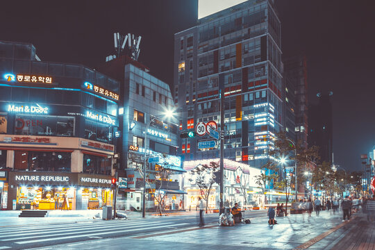 SEOUL, SOUTH KOREA - AUGUST 12, 2015: Lots of young people walking by a busy main street of Sinchon district at night - Seoul, Republic of Korea