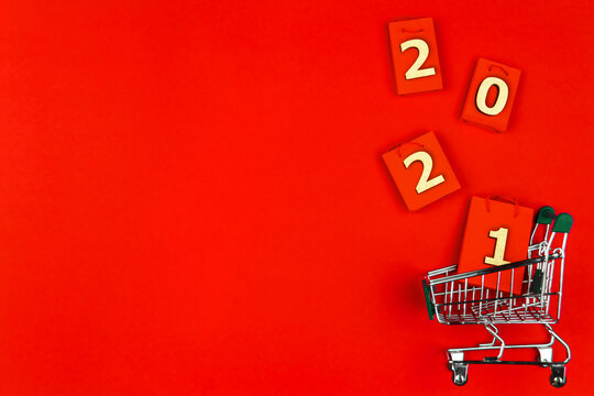 Small green trolley, mini cart on red background. Shopping bags, packages with numbers 2021. Preparing for Christmas, buying gifts, presents. Black friday sale. New year fair, market concept.