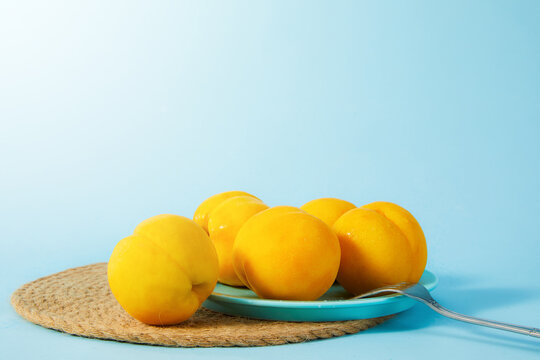Closeup shot of yellow peaches on a blue plate on a placemat