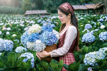 Wall Mural - Beautiful girl enjoying blooming blue hydrangeas flowers in garden, Chiang mai, Thailand.