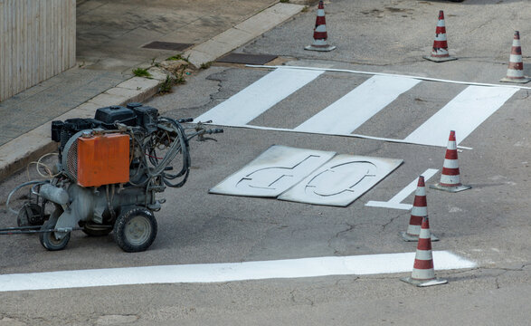 machine and workers at road construction use for road and traffic sign painting