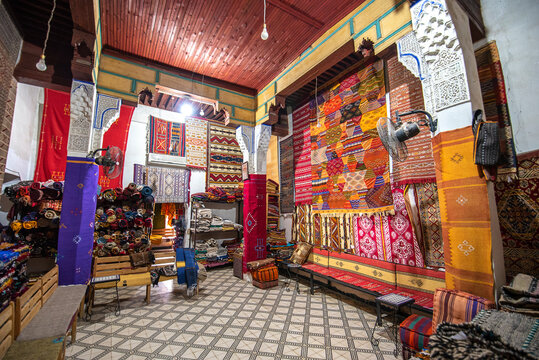 FES, MOROCCO - NOVEMBER 20, 2019: Interior of Carpet shop with colourful moroccan rugs and berber carpets on display in a souk market in the centre of medina. Fes El Bali (Maze of Fez)