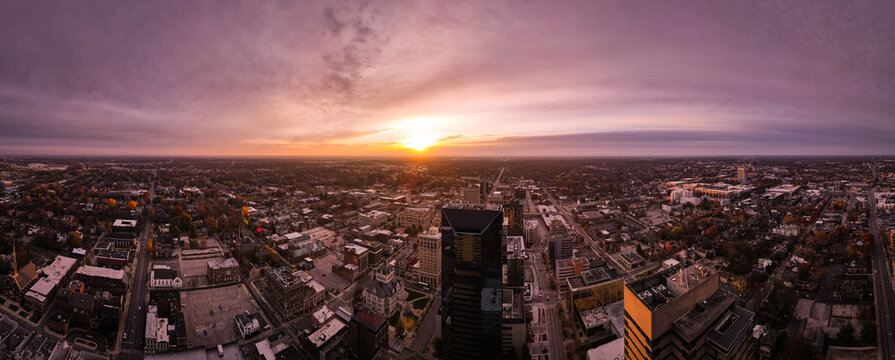 Looking into rising sun from Lexington, Kentucky downtown district with silhouette projections of tall office buildings