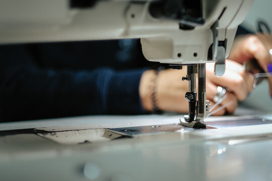 Closeup of female hands sewing gray leather on a machine