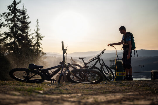 Mountain biker washing the mountain bikes in the sunset after a day of riding