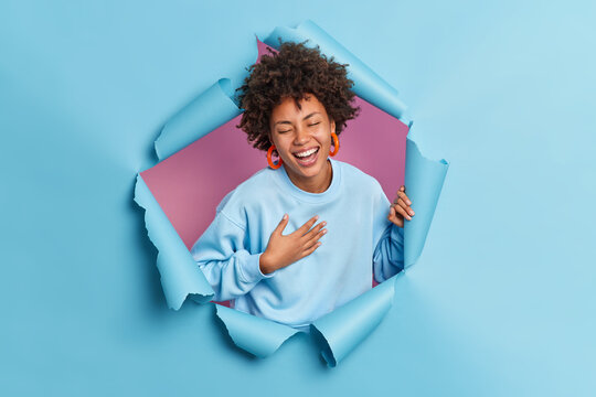 Optimistic joyful dark skinned young ethnic woman laughs out cannot stop giggling keeps hand on chest and smiles broadly closes eyes wears casual blue sweatshirt breaks through paper background