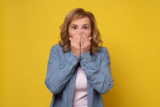 Shocked mature woman covers her opened mouth with hand, surprised with news.