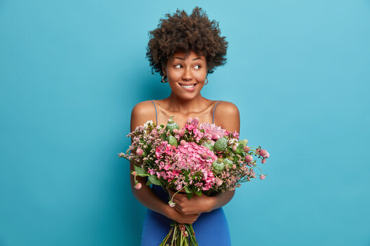 Pretty satisfied dark skinned young woman has Afro hair holds bunch of flowers bites lips and looks away receives bouquet on festive event poses against blue background. Girfriend enjoys date