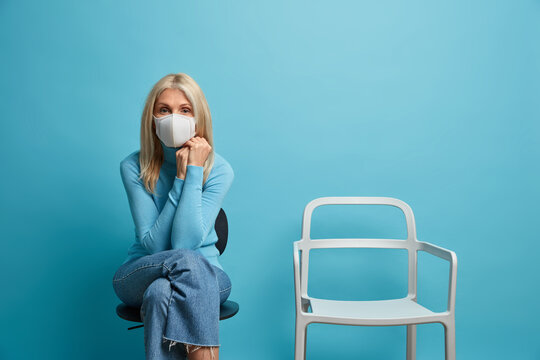 Stay at home and be safe. Serious blonde fifty years old woman wears protective mask on face avoids social contact poses alone near empty chair against blue wall. Pandemic quarantine concept