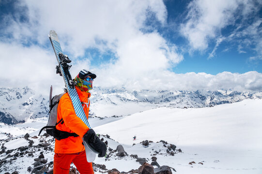 Portrait of a stern climber skier in sunglasses and a cap with a ski mask on his face. holds his skis on his shoulder and looks away against of Mount Elbrus