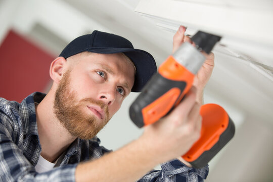 a young worker drilling ceiling