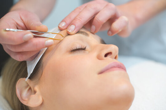 beautician doing eyebrows of a woman in cosmetic studio