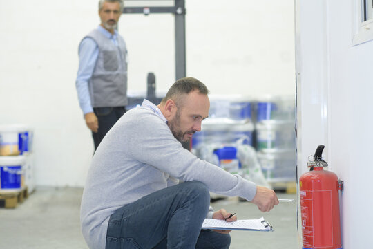 professional man checking a fire extinguisher