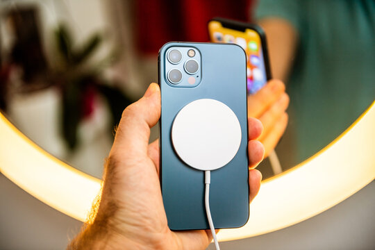 Paris, France - Nov 11, 2020: Man hand holding in front of mirror new iPhone 12 Pro Max 5G smartphone model by Apple Computers close-up of Pacific Blue mobile phone device charging with MagSafe