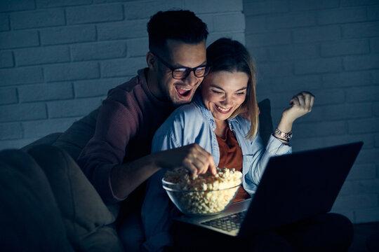 couple movie night tv laptop popcorn love watching entertainment man woman together popcorn happy