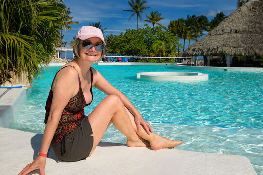 Smiling retired 60 year old woman sitting by the pool at a resort in Varadero Cuba