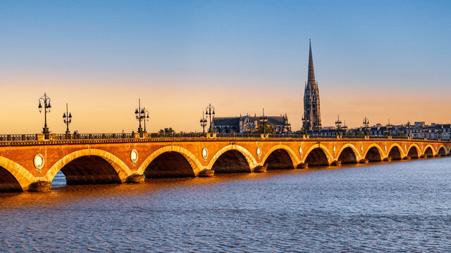 Bordeaux, France. Panoramic view of  Pont de Pierre, old stone bridge over the river Garonne, and Saint Michel cathedral at sunset.