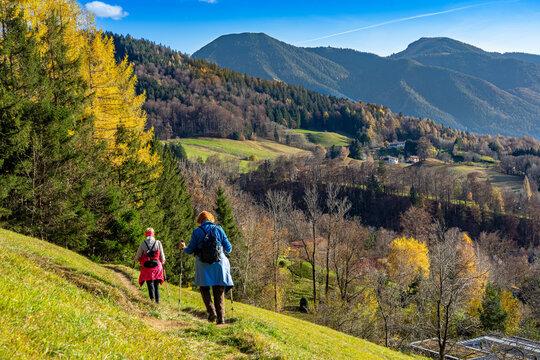 Herbst in Bayern: Zwei Seniorinnen wandern den Tegernseer Höhenweg mit Blick auf den Wallberg