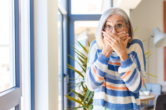 middle age woman covering mouth with hands with a shocked, surprised expression, keeping a secret or saying oops