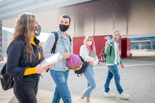Multiracial students with face mask walking speaking wearing protective mask during pandemic codvid19 at college campus - New normal lifestyle with social distance in coronavirus time
