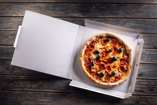 Pizza in a cardboard box on table ready to customer.