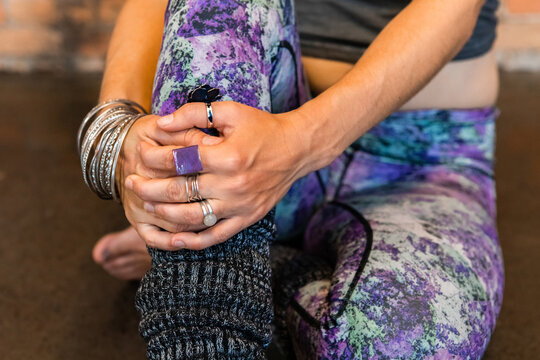 A closeup shot on the hands of a slim caucasian lady wearing vibrant gym pants, and knitted leg warmers with sliver jewelry during a yoga warmup